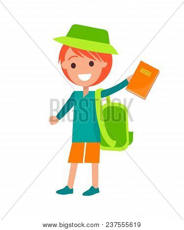 Boy With Red Medium Length Hair Wearing Green Hat And Backpack Holding Orange Hard Back Book In His