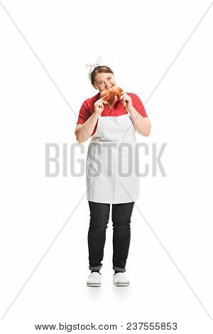 Portrait Of Cute Woman With Pastries In Her Hands Cooking A Loaf Of Bread In The Studio, Isolated On