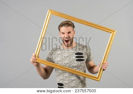 Man Shout With Picture Frame On Grey Background. Angry Macho With Beard Hold Wooden Photo Frame. Guy