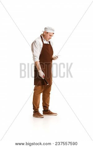 Serious Butcher Posing With A Knife And Mobile Phone Isolated On White Studio Background. The Young