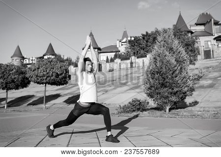 Man Stretching And Warming Up Muscles Before Workout. Fit Macho In Track Suit On Urban Landscape. He
