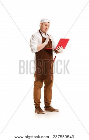 Serious Butcher Posing With A Laptop Isolated On White Studio Background. The Young Caucasian Male M