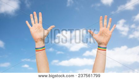 lgbt, same-sex relationships and homosexual concept - close up of male hands wearing gay pride awareness wristbands over blue sky and clouds background