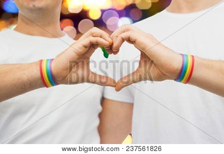 lgbt, same-sex love and homosexual relationships concept - close up of happy male couple wearing gay pride rainbow awareness wristbands showing hand heart gesture over lights background