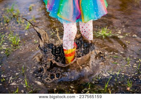 Crop View From Above Of Girl In Colorful Skirt And Gumboots Jumping In Big Puddle Splashing Water Ar