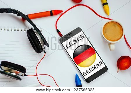 Smartphone With German Flag And Headphones. Concept Of German Learning Through Audio Courses