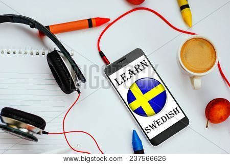 Smartphone With Swedish Flag And Headphones. Concept Of Swedish Learning Through Audio Courses