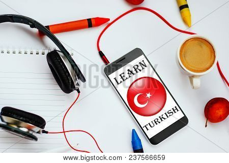 Smartphone With Turkish Flag And Headphones. Concept Of Turkish Learning Through Audio Courses