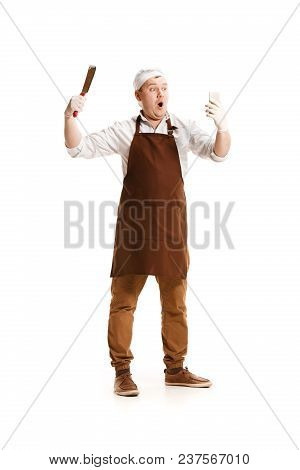 Smiling Butcher Posing With A Knife And Mobile Phone Isolated On White Studio Background. The Young