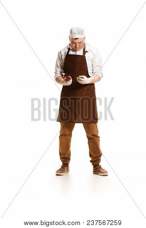Sad Butcher Posing With A Knife And Mobile Phone Isolated On White Studio Background. The Young Cauc