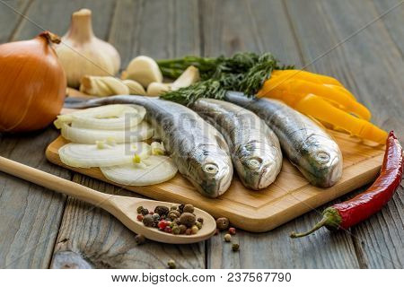 Raw Fish On Kitchen Table With Ingredients For Cooking, Top View. Three Whole Char Fish. Healthy Foo