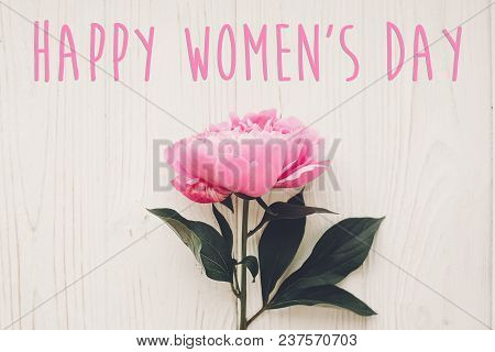 Happy Women's Day Text On Pink Peonies Bouquet On Rustic White Wooden Background In Light, Top View.