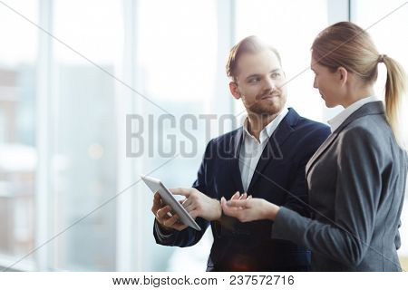 Businessman pointing at touchpad and showing something to businesswoman