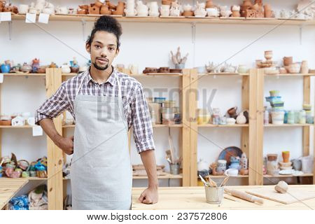 Portrait of young man in apron standing in workshop with handmade clay products and looking at camera