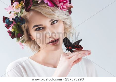 Tender Girl Posing In Flower Wreath With Alive Butterfly On Hand, Isolated On Grey