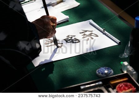 Japanese Calligraphy, Unrecognizable Person Writing Kanji Characters With Ink Brush On Paper, Englis