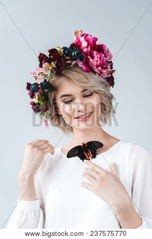Smiling Girl Posing In Flower Wreath With Alive Butterfly On Neck, Isolated On Grey