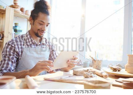 Young mixed race male ceramist watching pottery tips on digital table and smiling while sitting in workshop
