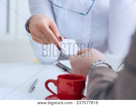 Close-up Of Business Woman Giving Visiting Card To Male Colleague At Desk In Office