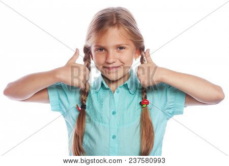 happy little girl child standing isolated over white background. Looking camera showing thumbs up. Lifestyle and people concept.