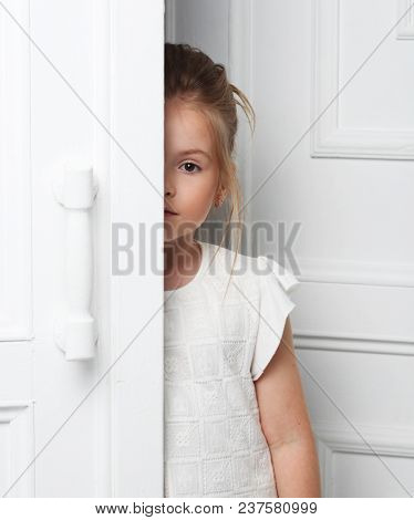 Children's fashion. A beautiful, thoughtful serious blonde girl in white clothes peeks out from behind the door. Cleanliness and innocence.