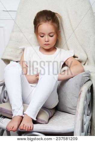 Girl fashion portrait. Child model sitting in chair.