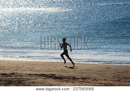 Silhouette Of A Young Man Doing A Sprint Along The Beach, Back Lit