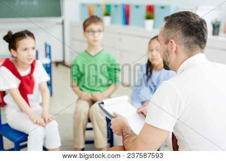 Professional male teacher giving lesson to elementary school children sitting on chairs in classroom and listening to him attentively