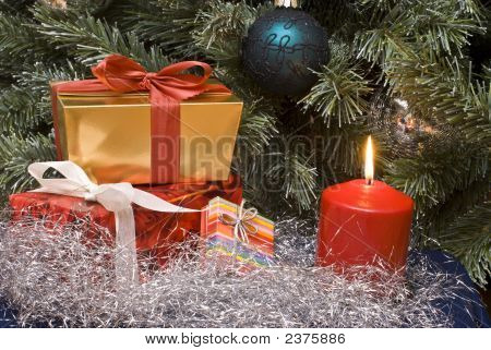 Gifts and burning candle under a Christmas tree poster