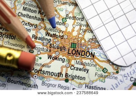 London City Of Great Britain In The Center Of The Geographic Map, Pencils And Paper Sheet