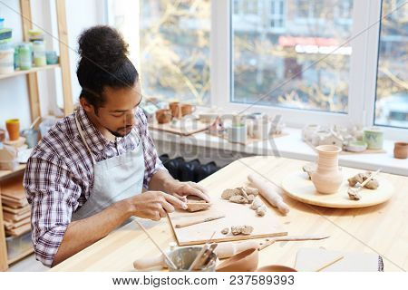 Young concentrated mixed-race male ceramist preparing clay while modeling pots in workshop