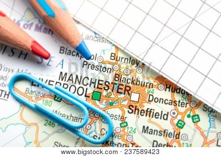 Manchester City Of Great Britain In The Center Of The Geographic Map, Pencils And Paper Sheet