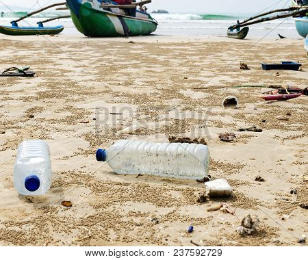 Empty Used Plastic Bottles And Other Waste Thrown Out At The Sea Beach On Background Is Fishing Boat