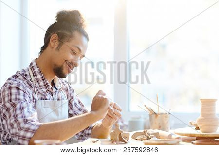 Portrait of young mixed-race male potter making clay handicrafts in workshop and smiling  happily