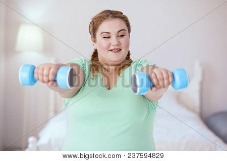 Follow Directions. Plump Young Woman Following Accuracy Of Her Moves While Doing Exercises With Dumb