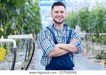 Waist Up Portrait Of Cheerful Plantation Worker Posing Standing With Arms Crossed And Looking At Cam