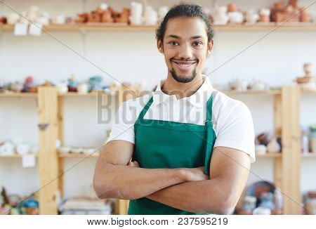 Portrait of young mixed race man in apron smiling at camera happily while  standing in pottery workshop with his hands crossed