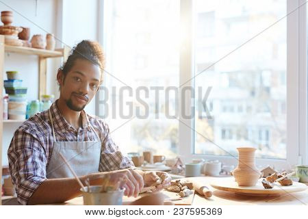 Portrait of handsome confident mixed race man in apron looking at camera while making clay vases in workshop
