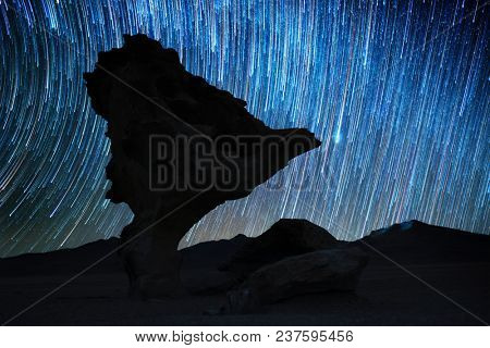 Rock formation named Arbol de Piedra at night with starry sky on the background. Bolivia