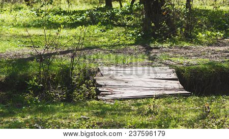 Wooden Bridge Over A Small Ravine In The Forest
