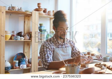 Young mixed-race male potter in apron sitting at table and modeling clay souvenirs in workshop