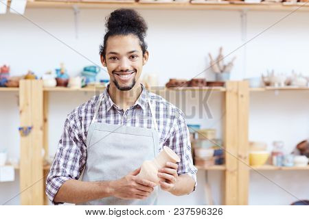 Portrait of young mixed race man in apron standing in workshop with handmade clay vase and smiling at camera happily