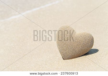 Heart Made Of Sand With Shadow On Sandy Beach Background Against Sea Wave Foam, Saint Valentines Day