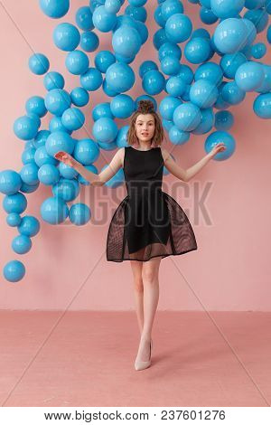 Happy Beautiful Young Girl In Black Dress Dancing With Arms Raised And Winking. Full Length Studio S