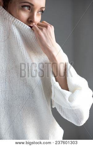 Sensual Young Woman Taking Off White Sweater And Looking Away On Grey