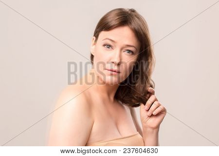 Close Up Image Of Young Woman Standing Half Turn And Touching Hair. Beauty Concept. Mid Age Woman Ov