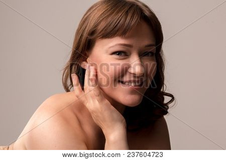 Charming Female Model Sitting Half Turn And Gently Touching Her Face. Beauty Concept. Mid Age Woman