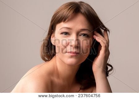 Attractive Woman With Natural Makeup Gently Touching Her Hair. Posing On Camera. Beauty Concept. Mid