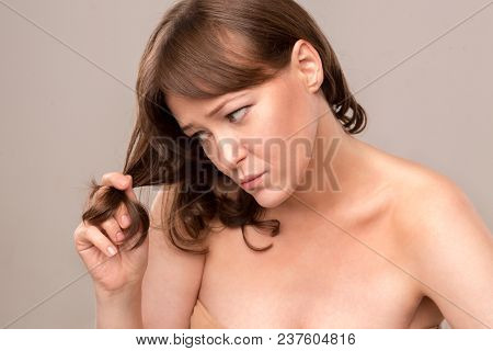 Gorgeous Woman Standing Half Turn And Touching Her Hair. Looking At It With Disappointment. Mid Age