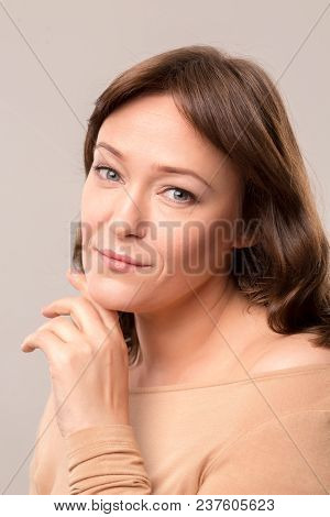 Mid Age Woman Over 35 Years Old Beauty Concept. Close Up Portrait Of Beautiful Woman Gently Touching